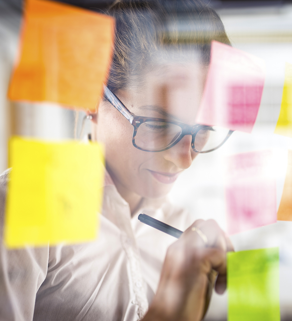 Graphic designer is putting her ideas on a sticky note on a glass wall. She is smiling and focused on writing.